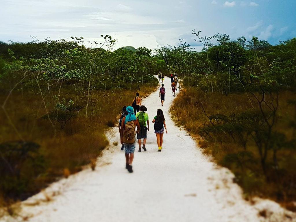 Pessoas fazendo passeio no parque nacional da Chapada dos Veadeiros caminhando pelo cerrado com guia local