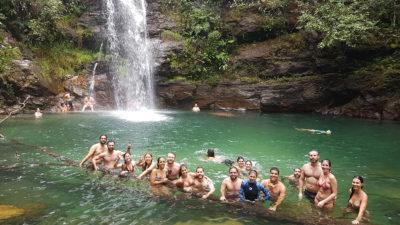 Grupo de turistas posando para foto em cima de uma árvore no poço da cachoeira Santa Bárbara