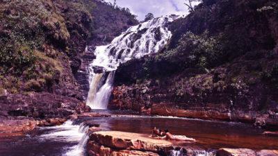 Turistas pegam sol na última piscina natural das cataratas dos Couros no período de seca com as cachoeiras almécegas 1000 e do Parafuso no fundo na Chapada dos Veadeiros